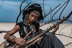 Beautiful young stylish tribal woman in oriental costume playing. Sitar royalty free stock image