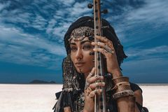 Beautiful young stylish tribal woman in oriental costume playing sitar outdoors. Close up royalty free stock image