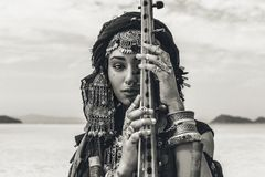 Beautiful young stylish tribal woman in oriental costume playing sitar outdoors. Close up royalty free stock images