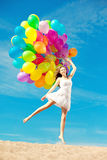 Beautiful young stylish woman with ainbow balloons in hands agai Royalty Free Stock Photos