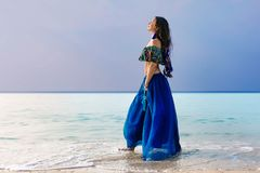 Beautiful young stylish woman in blue skirt on the beach Royalty Free Stock Photos