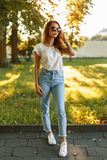 Beautiful young stylish woman in the fashion brand clothing. Standing in the park at sunset royalty free stock image