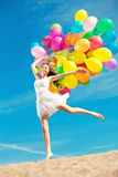 Beautiful young stylish woman with multi-colored rainbow balloon Stock Image