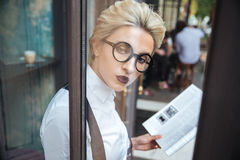 Beautiful young stylish woman reading book in cafe Royalty Free Stock Image