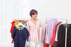 Beautiful young stylist choosing clothes stock images