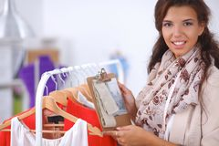 Beautiful young stylist near rack with hangers Stock Photo