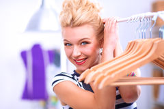 Beautiful young stylist near rack with hangers royalty free stock photo