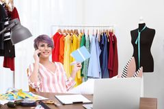 Beautiful young stylist talking on phone at workplace near rack stock images