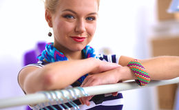 Beautiful young stylist woman near rack with hangers Royalty Free Stock Photos