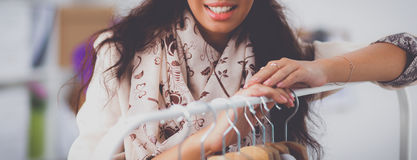Beautiful young stylist woman near rack with hangers. Beautiful young stylist near rack with hangers Royalty Free Stock Photos