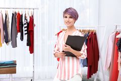 Beautiful young stylist at workplace near rack with clothes. royalty free stock photo