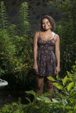 Beautiful young in sundress standing in garden Stock Photography