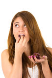 Beautiful young supersticious woman eating grapes Stock Photography