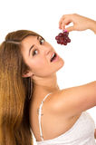 Beautiful young supersticious woman eating grapes Royalty Free Stock Photos