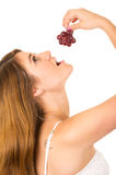 Beautiful young supersticious woman eating grapes Royalty Free Stock Photo
