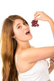 Beautiful young supersticious woman eating grapes Stock Photos