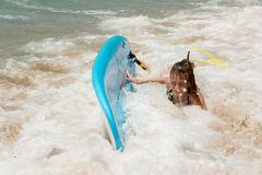 Beautiful young surfer girl falling off the surfboard Royalty Free Stock Images