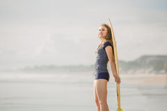 Beautiful young surfer girl stays on the beach at Royalty Free Stock Photos