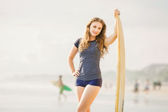 Beautiful young surfer girl stays on the beach at Stock Images