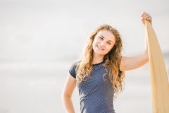 Beautiful young surfer girl stays on the beach at Stock Photo
