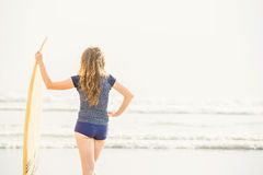 Beautiful young surfer girl stays on the beach at Stock Image