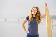 Beautiful young surfer girl stays on the beach at Royalty Free Stock Photo