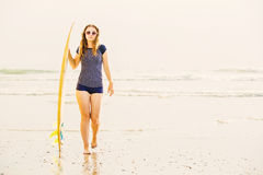 Beautiful young surfer girl stays on the beach at Stock Photography