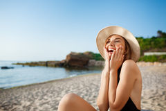 Beautiful young surprised girl in hat rests at morning beach Royalty Free Stock Photos