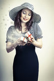 Beautiful young surprised woman opening small magical gift and s. Birthday and holiday concept.Beautiful young surprised woman opening small magical gift and Stock Photo
