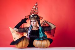 Beautiful young surprised woman in witches hat and costume holding pumpkin. Beauty Woman posing with Pumpkin and. Halloween hat. Halloween dresses and witch royalty free stock photography