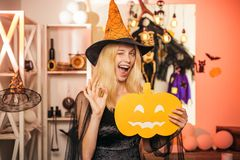 Beautiful young surprised woman in witches hat and costume holding pumpkin. Surprised woman in witches hat and short. Dress. Indoor portrait of cute young witch stock photos