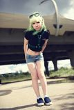 Beautiful young swag woman with green hair posing near highway road Royalty Free Stock Image