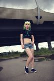 Beautiful young swag woman with green hair posing near highway road Royalty Free Stock Photos