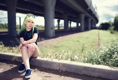 Beautiful young swag woman with green hair posing near highway road Royalty Free Stock Images