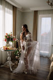 Beautiful young sweet blonde girl with a wedding bouquet in the hands of the boudoir in a white dress with evening hairstyle walks Royalty Free Stock Photos