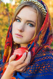 Beautiful young sweet girl in a headscarf with the rim on the head with a red Apple in his hand, like a fairy tale character Royalty Free Stock Image