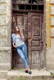 Beautiful young sweet girl with red hair in jeans standing near the door of the old city Royalty Free Stock Photography