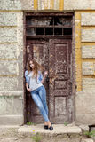 Beautiful young sweet girl with red hair in jeans standing near the door of the old city Royalty Free Stock Photo