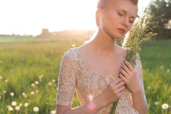 Beautiful young sweet girl in a white dress with hair on the head oblique walks in a field at sunset. Beautiful young sweet girl in a white dress with hair on Royalty Free Stock Image