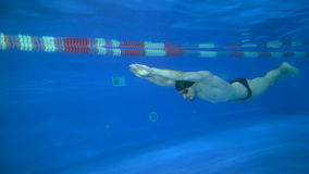 Beautiful young swimmer swims under the water only with his feet crawl. Underwater view in 4K. Beautiful young swimmer swims under the water only with his feet stock video footage