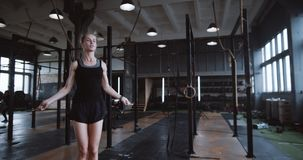 Beautiful young tall blonde woman working out with jump rope in large gym slow motion. Active and healthy lifestyle. Beautiful young tall blonde woman working stock video footage