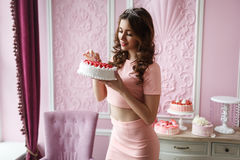 Beautiful young tall girl in a pink dress holding a cake and smiling. Pink interior style Royalty Free Stock Image