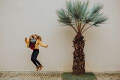 A beautiful young tanned girl jump near a yellow wall in the south. Fashionable dress, bright make-up, tan. Palms, royalty free stock images