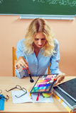 Beautiful young teacher making-up Stock Photography
