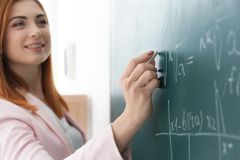 Beautiful young teacher writing on blackboard royalty free stock images