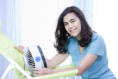 Beautiful young teen enjoying cool fan breeze Stock Photo