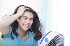 Beautiful young teen enjoying cool fan breeze Stock Photography
