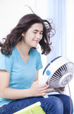 Beautiful young teen enjoying cool fan breeze Stock Images
