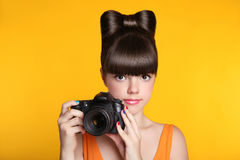 Beautiful young teen girl with camera taking a photo. Pretty mod Stock Images