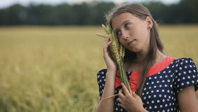 Beautiful young teen girl with ears of wheat in a wheat field. stock footage